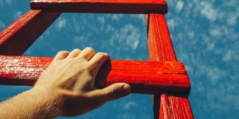 hand holding onto red ladder with sky in the background