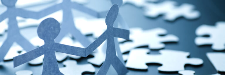 Puzzle pieces scattered on a table with cut out of people holding hands standing on top
