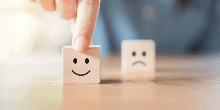 person holding cube with smiling face with frowning face cube in background