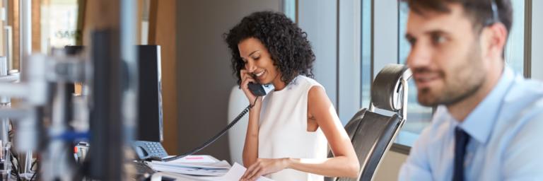 Woman sitting down talking on a desk phone