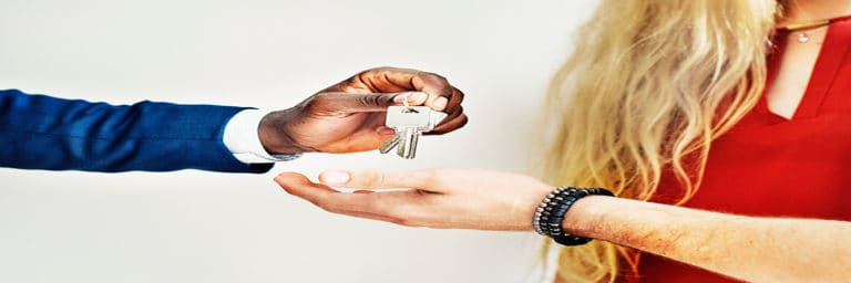 realtor handing keys to new home owners