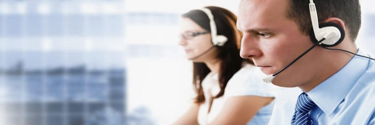 man and woman at computers using phone headsets