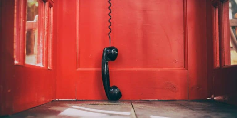 Old Telephone hanging from a red door. It probably needs to be upgraded to Switchvox