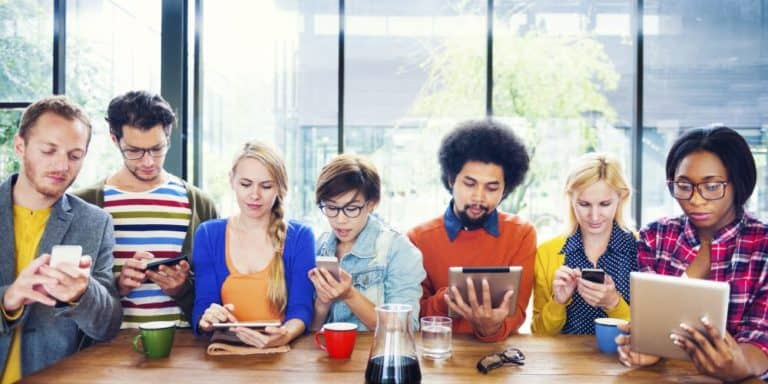 young adults sitting at table using mobile phones and tablets