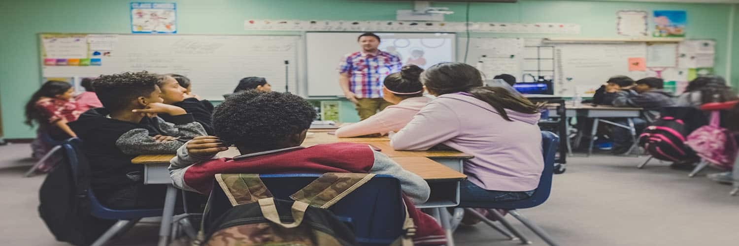 students in classroom listening to teacher