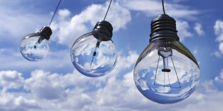 three lightbulbs in front of blue sky with clouds