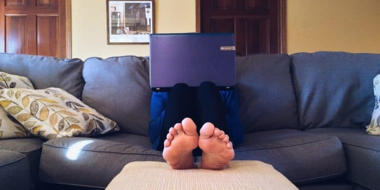 person sitting on couch using laptop