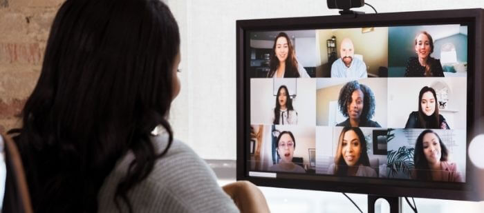Woman meeting virtually and collaborating with team while working remotely